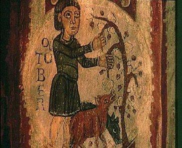 Reproducción medieval de un campesino alimentando con bellotas unos cerdos